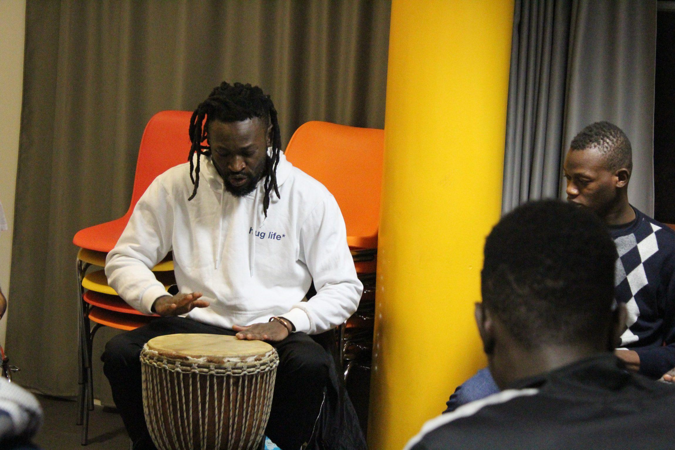Un musicien joue du djembé devant un groupe de jeunes